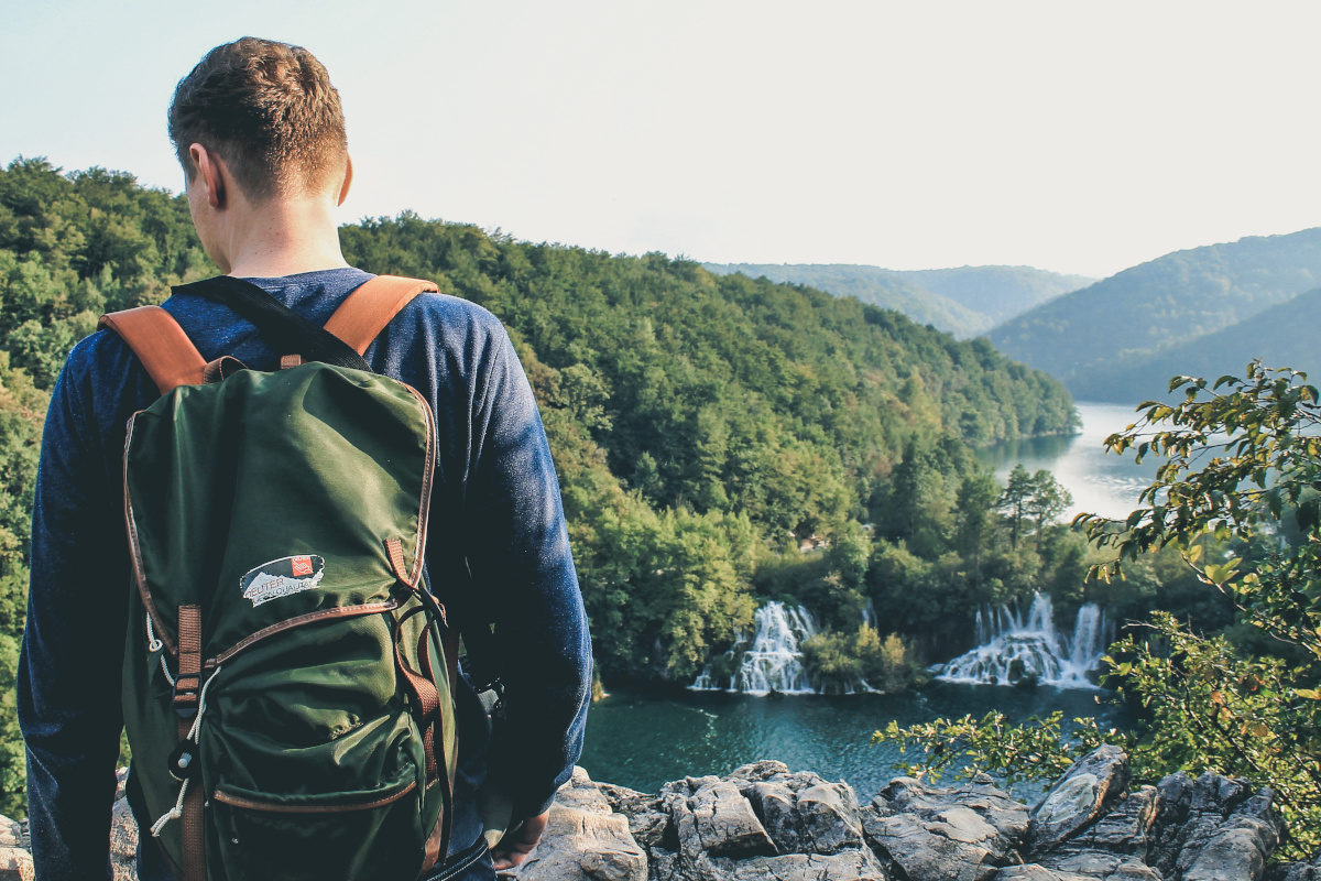 Adventurer with backpack looks at waterfalls in plitvice lakes