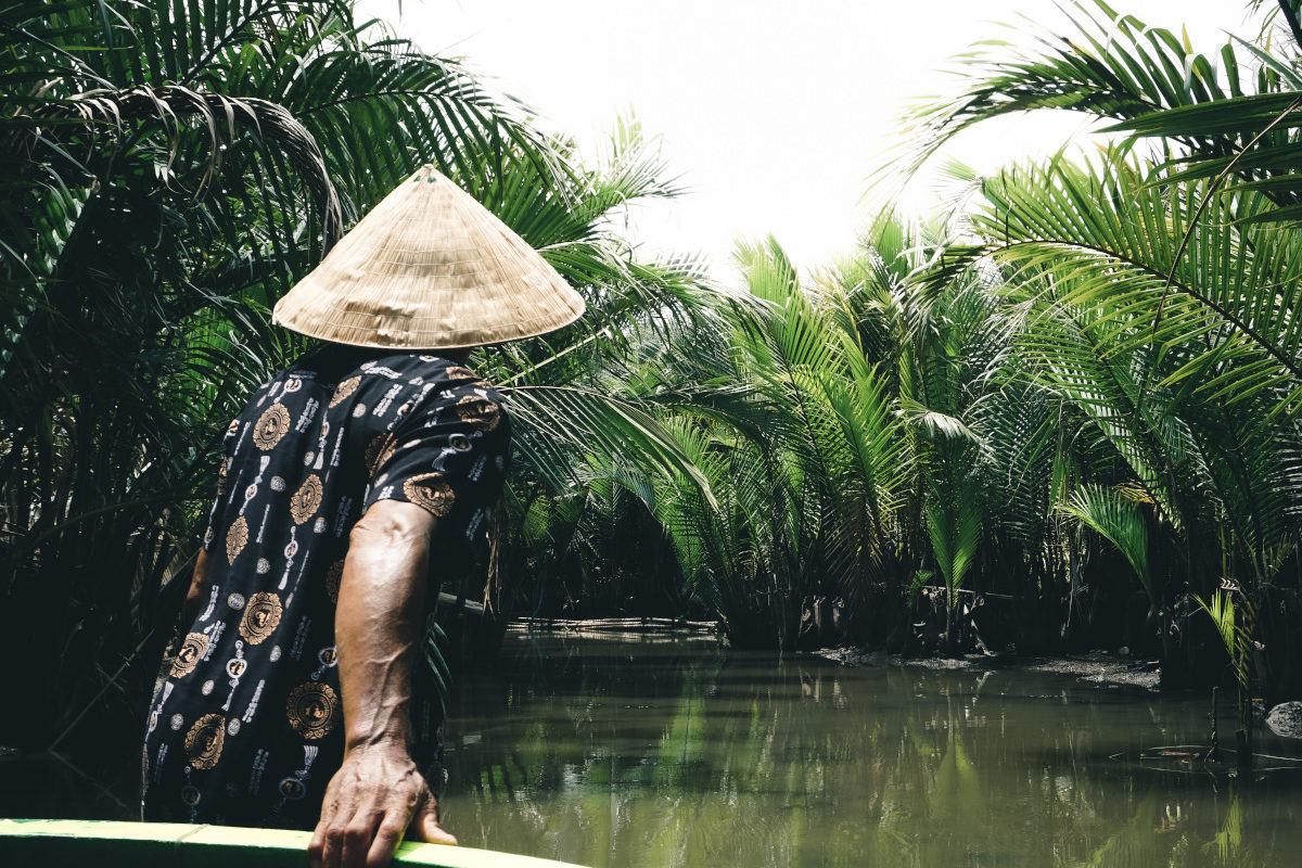vietnamese man pulls traditional boat in the jungle in asia