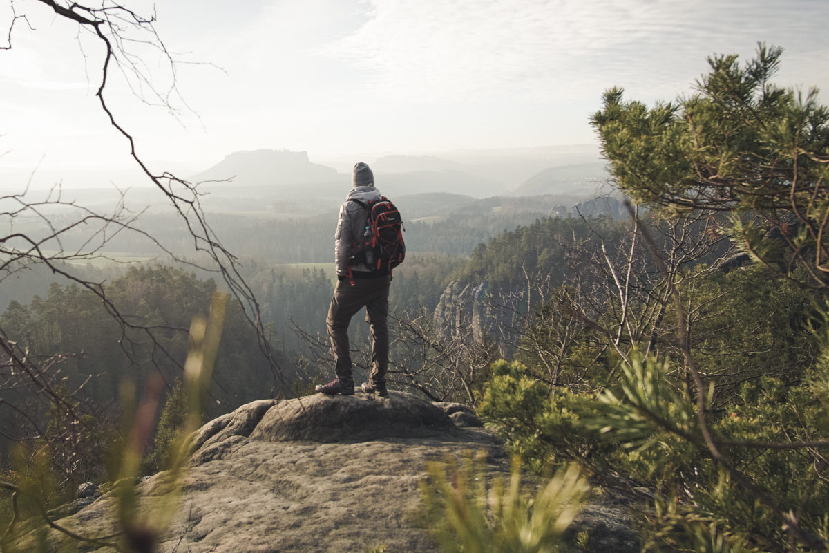 Adventurer stands on rock formation in national park in Germany