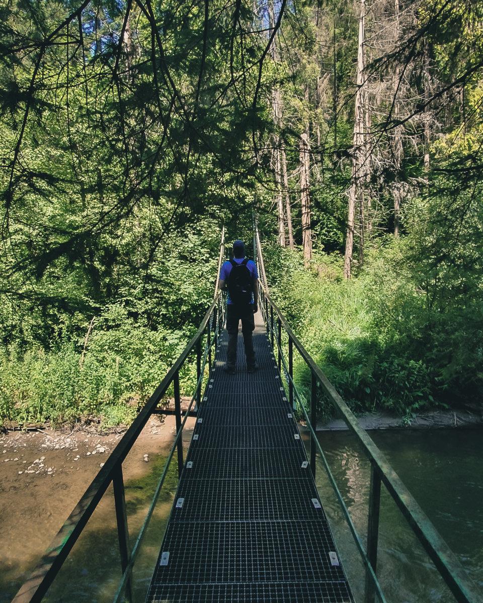 Hiker on a bridge over the hornadu river