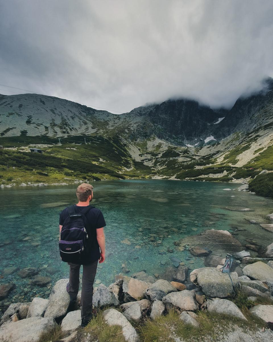 Tourist stands on glacier lake