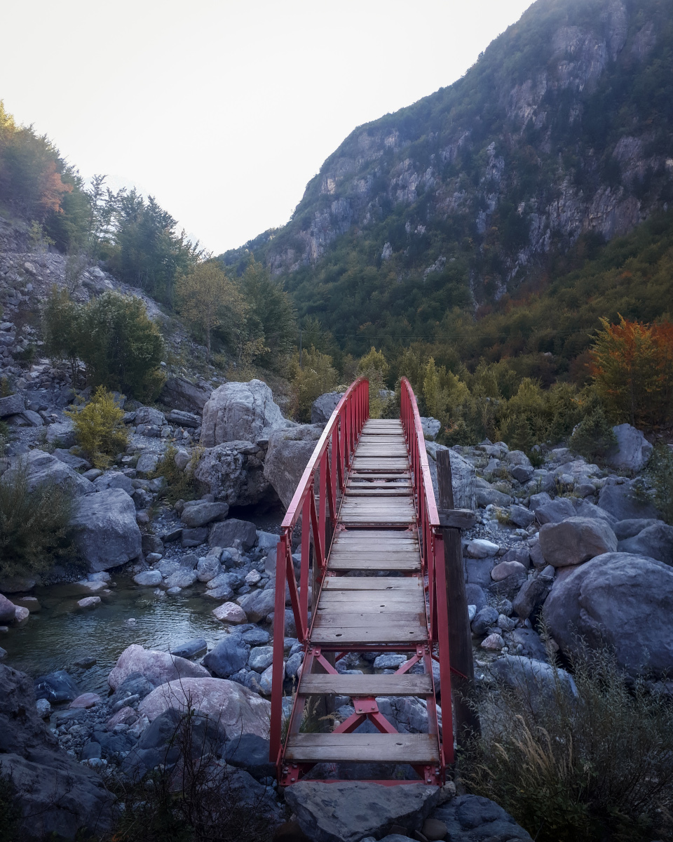 Red bridge over a river in the mountains