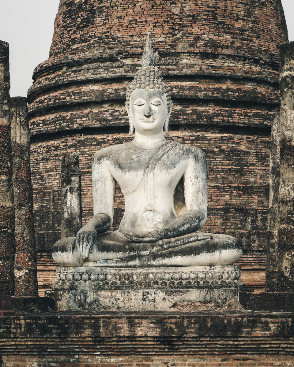 Bright Buddha statue in front of a temple