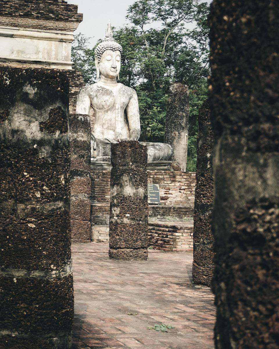 Buddha statue behind stone pillars