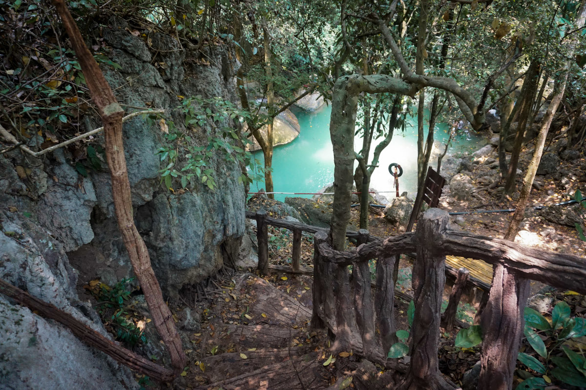 Wooden stairs in the jungle to a turquoise pool