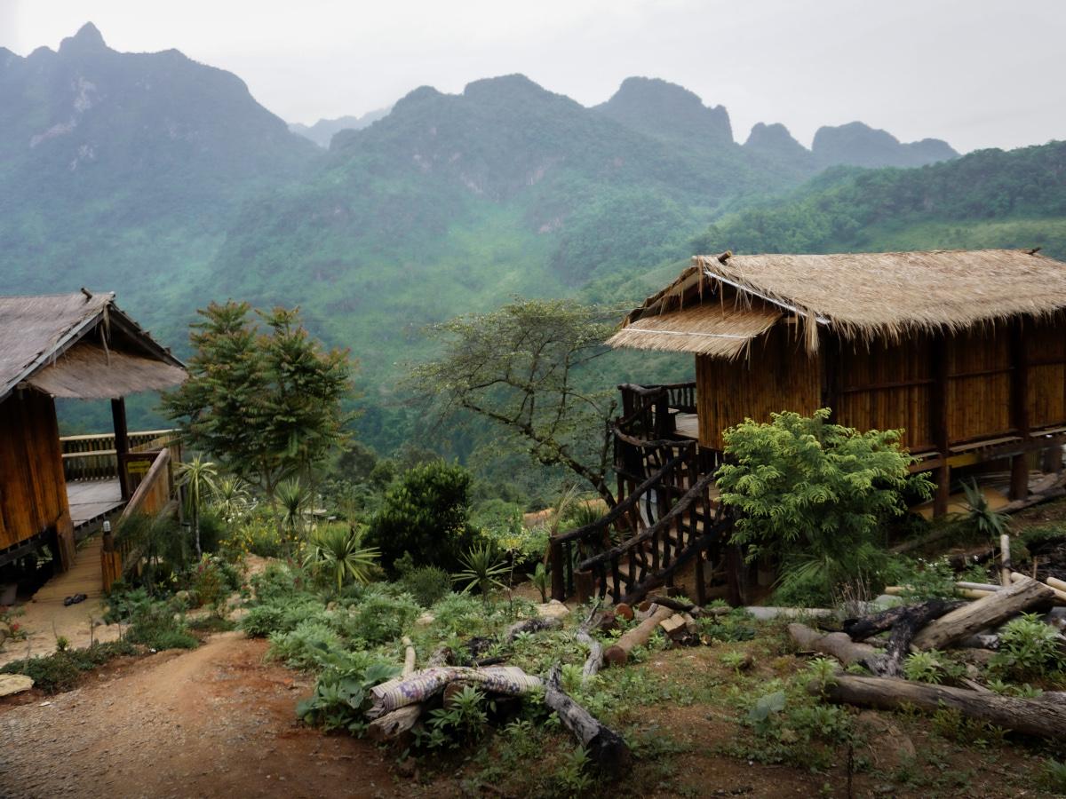 Two wooden huts on a mountainside in Lisu village