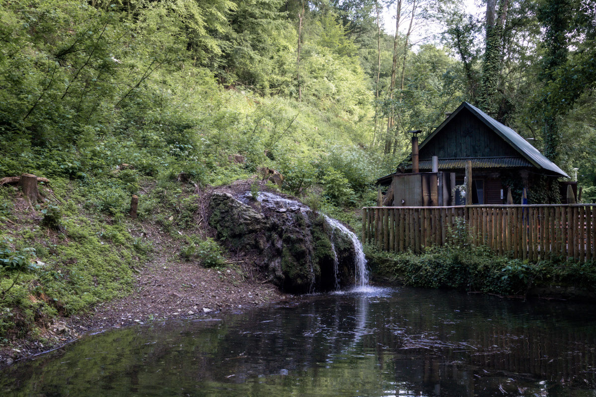 Pond with a small waterfall in front of a restaurant