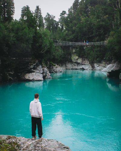 Traveler stands in front of glacier river in New Zealand