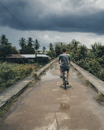 Solo traveler on a bridge cycles into an adventure